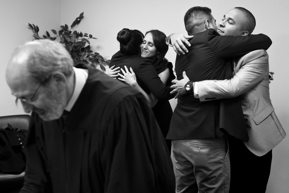Judge Steve Bernstein shuffles through papers as Elena Piloni hugs Jenny Aniciete, left, and Rey Cuellar hugs Julian Longoria after Rey and Jenny were married at City Hall on Tuesday, Nov. 12, 2013 in Chicago. Julian Longoria and Elena Piloni, left, are long-time friends of Rey and Jenny and were witnesses to the wedding. Jenny jokingly said they chose to get married on 11-12-13 so Rey could remember the date. They plan to have a full ceremony on Rey's birthday, Jan. 16, 2015 for their family and friends. (Adam Wolffbrandt/ Chicago Tribune)